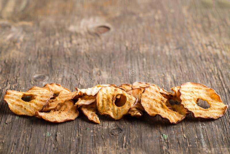 Casse-croûte sain La pomme sèche savoureuse sonne des puces sur le backgroun en bois images libres de droits