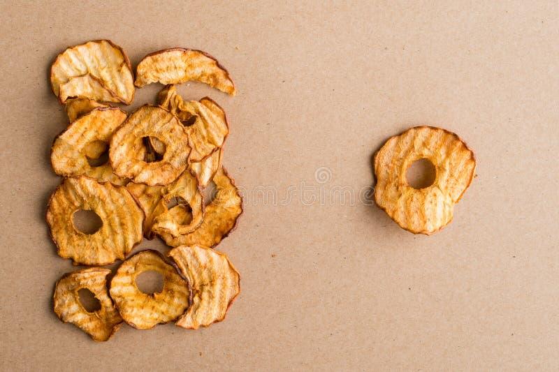 Casse-croûte sain La pomme sèche savoureuse sonne des puces sur le fond clair images stock