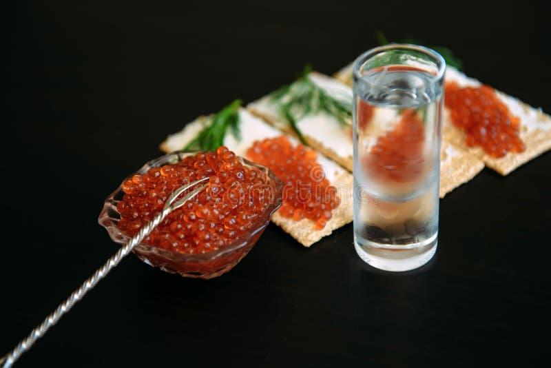 Casse-cro?te avec le caviar et le verre rouges de vodka froide sur le fond en bois noir Spiritueux et d?marreur traditionnel photo libre de droits