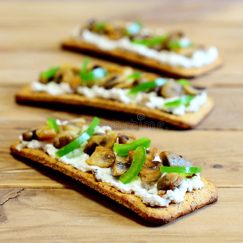 Casse-croûte délicieux avec des champignons et des légumes Champignons frits et paprika vert frais sur les biscuits minces photo libre de droits