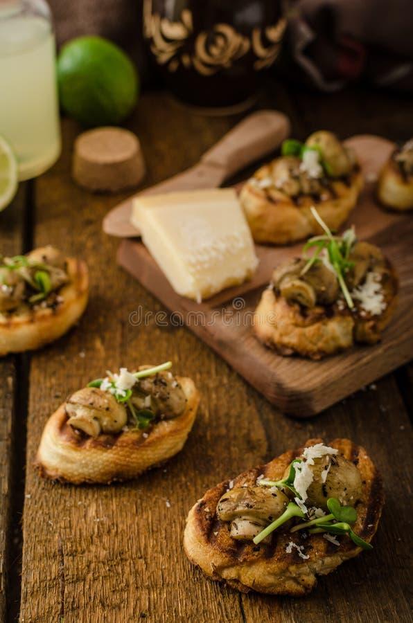 Casse-croûte de champignon sur la baguette grillée photo stock