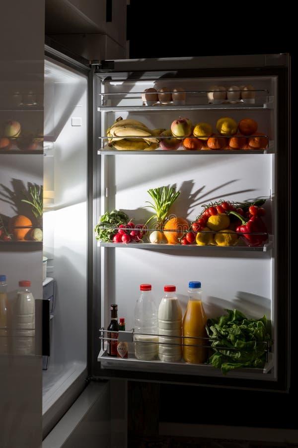Casse-croûte de minuit, regardant dans le réfrigérateur photo libre de droits
