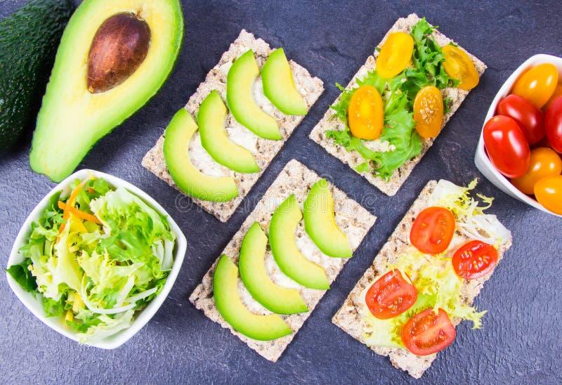 Casse-cro?te sain du biscuit entier de pain croustillant de seigle avec les tomates-cerises, l'avocat et la salade Nutrition appr image libre de droits
