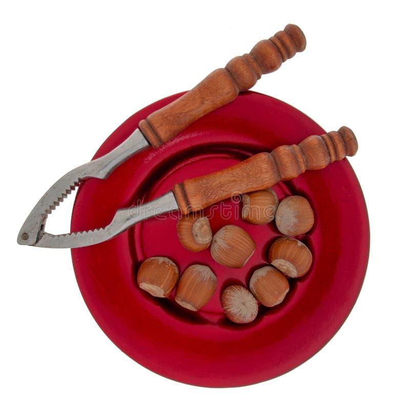 Casse-noix et noisettes entières du plat rouge de fête, d'isolement sur le fond blanc Noël typique, festin saisonnier photos libres de droits