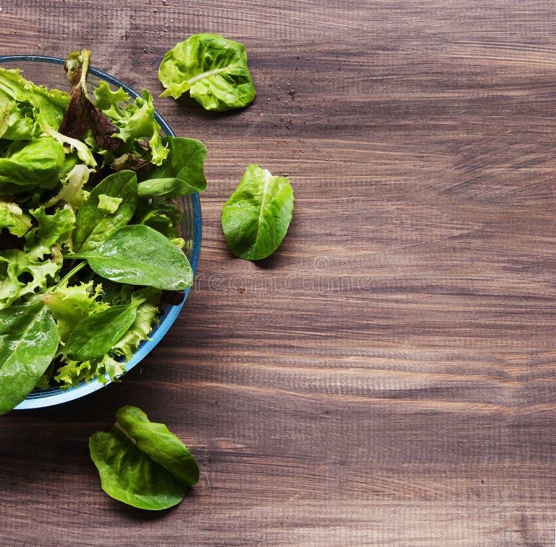 Casserole avec de la salade verte sur les conseils en bois photo libre de droits