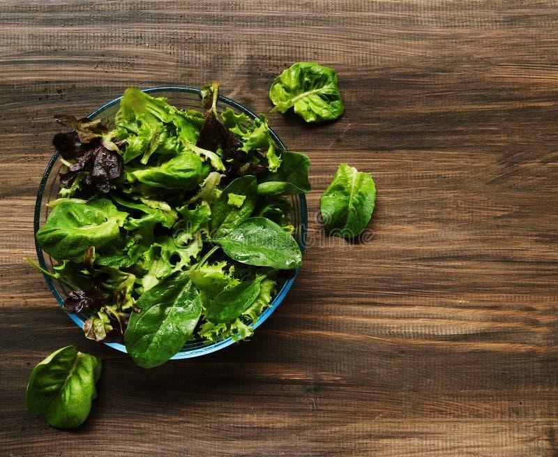 Casserole avec de la salade verte sur les conseils en bois photos stock