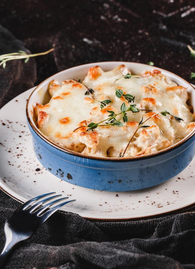 Casserole with cheese, broccoli, cauliflower and herbs in bowl over dark background with napkin. Healthy dinner or lunch setting, stock photo