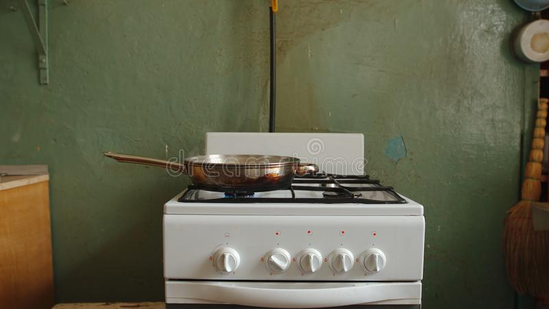 Casserole en acier sur une cuisinière à gaz dans une vieille cuisine d'un appartement communal image libre de droits