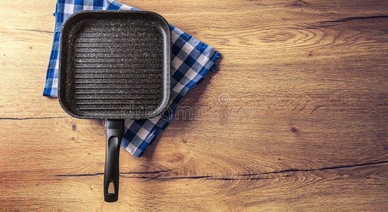 Casserole en céramique de gril sur la table en bois de cuisine avec la nappe à carreaux bleue image libre de droits