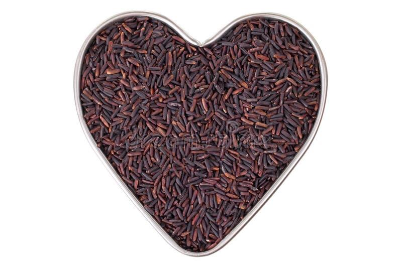 Casserole en forme de coeur de bidon complètement de grains crus de riz de Riceberry dans les reddis photo stock