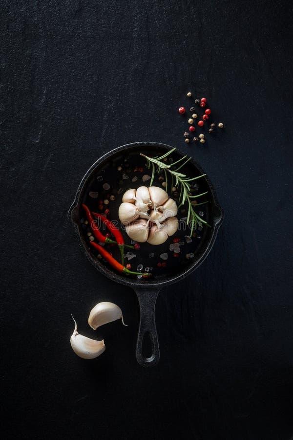 Casserole et épices de fonte sur le fond culinaire en pierre noir fro images libres de droits