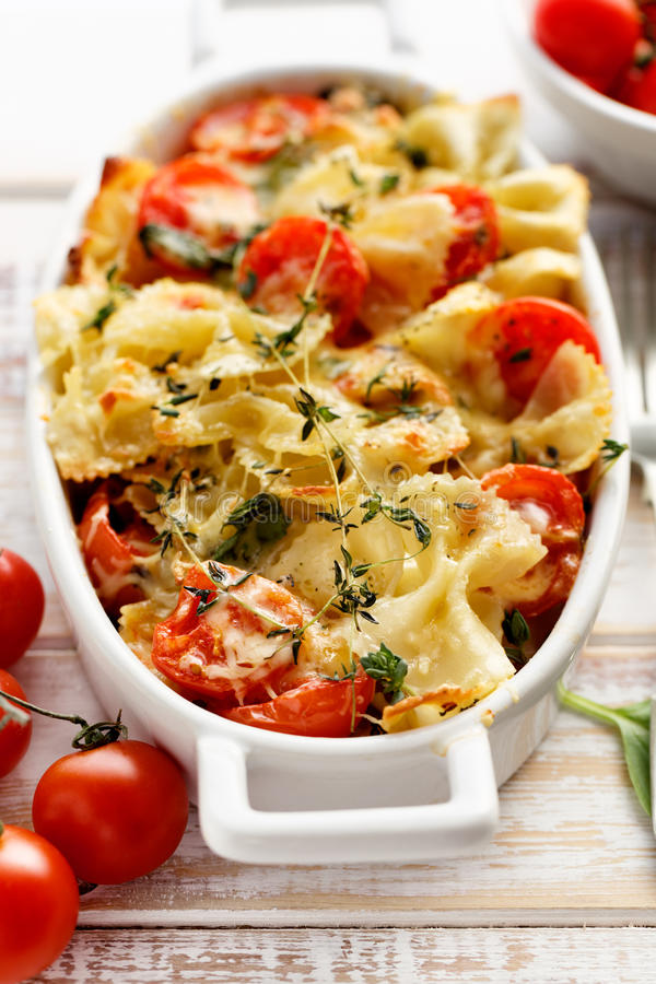 Casserole with farfalle pasta, cherry tomato, mozzarella cheese and thyme stock image