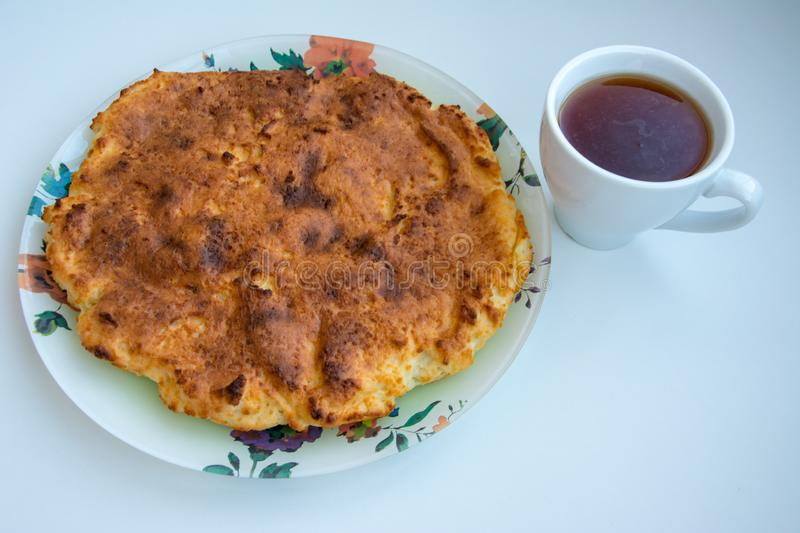 Casserole on a plate with a cup of tea on a white background. royalty free stock photography