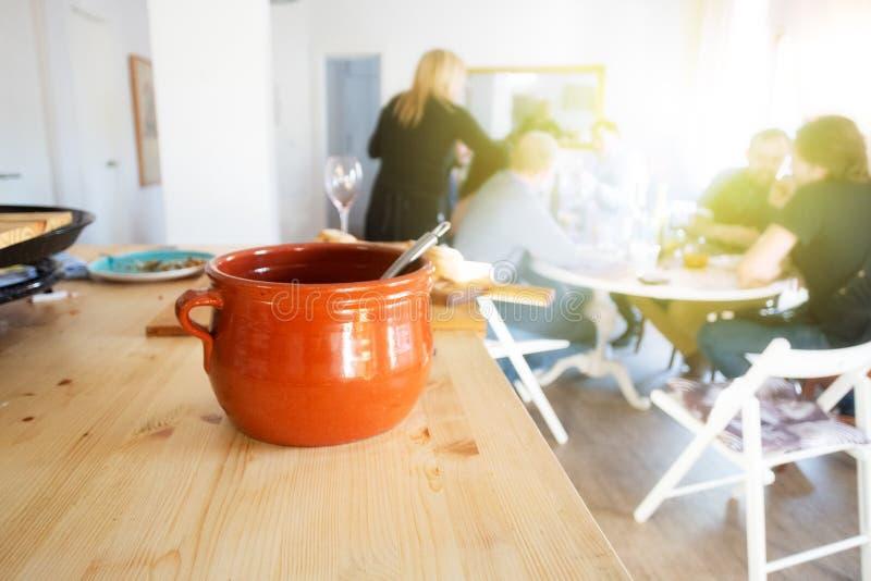 Casserole sobre a mesa e pessoas sentadas e comendo comida perto da janela depois da aula culinária principal fotos de stock royalty free