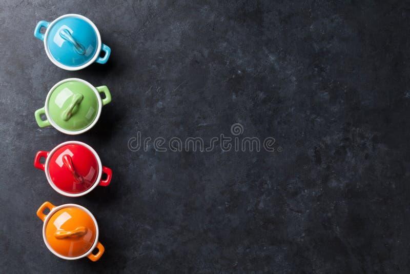 Casseroles colorées sur la table en pierre photo stock