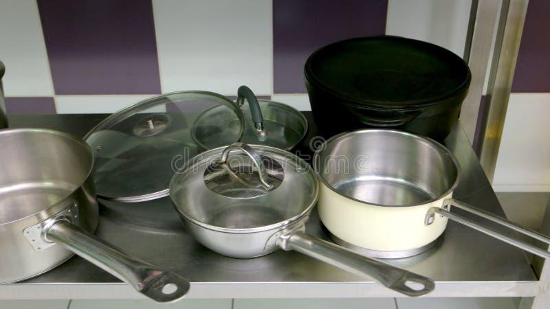 Casseroles d'acier inoxydable dans la table de cuisine image libre de droits
