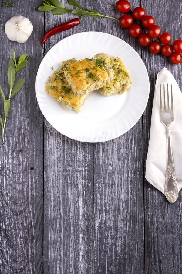 Casseruola casalinga deliziosa dello zucchini, del riso e del formaggio su un piatto bianco su un fondo di legno fotografia stock libera da diritti