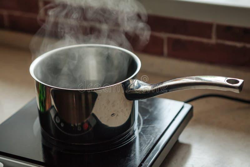Casseruola con acqua bollente sulla stufa di cucina elettrica immagine stock libera da diritti