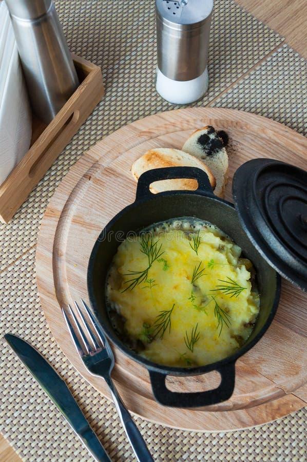 Casseruola con le patate e le parti della carne in un vaso del ghisa fotografie stock