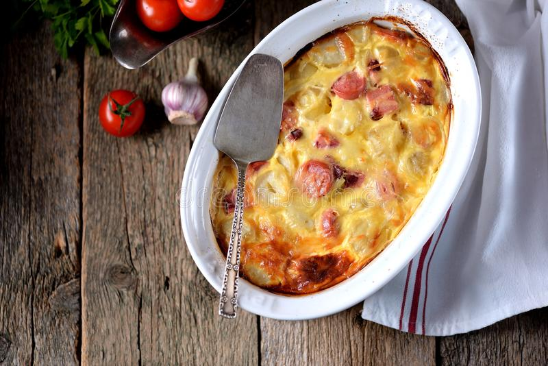 Casseruola della patata con le salsiccie, le cipolle ed il formaggio su un vecchio fondo di legno Stile rustico immagine stock