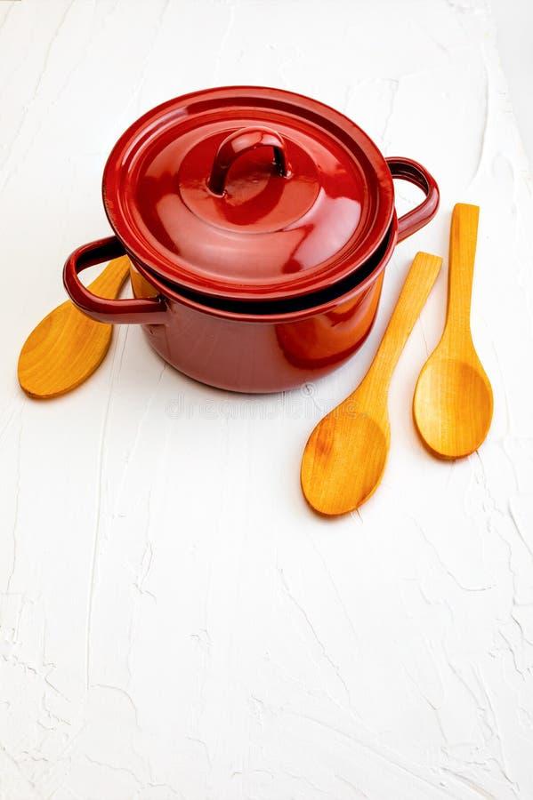 Casseruola e cucchiai di legno su fondo bianco con struttura Spazio per inserire il vostro testo qui Lettera per i ristoranti fotografia stock