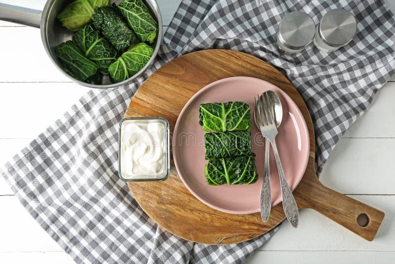Casseruola e piatto con le foglie del cavolo farcito sulla tavola immagini stock