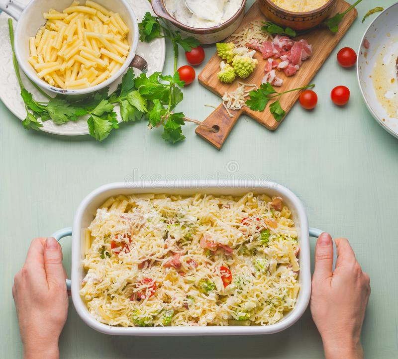 Casseruola femminile della pasta della tenuta della mano con il pomodoro, il bacon ed il formaggio, vista superiore immagini stock libere da diritti