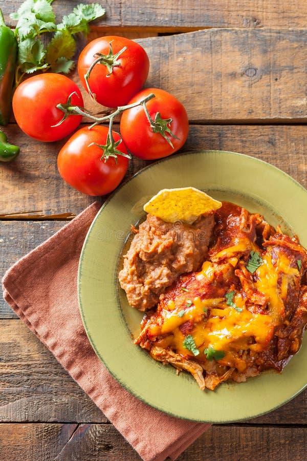 Casseruola messicana dell'alimento del Enchilada del pollo servita su verde di Rusitc fotografia stock