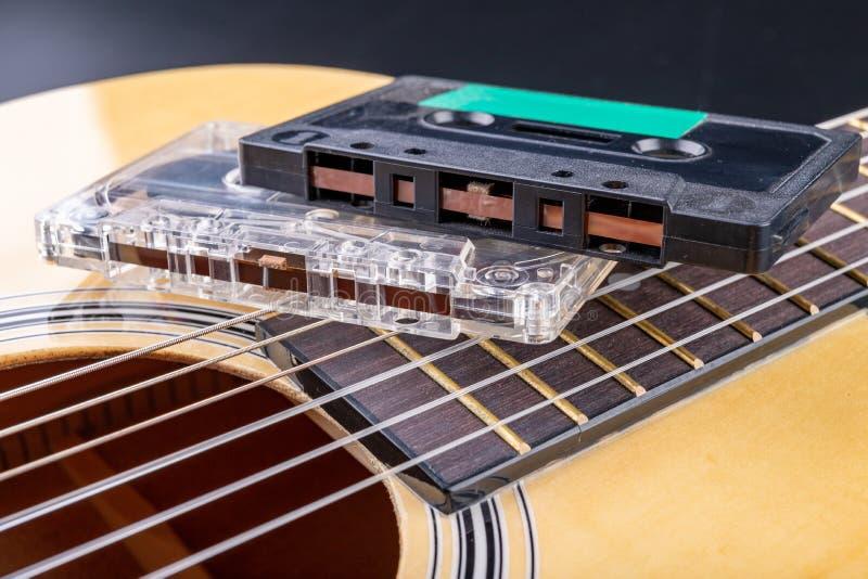 Cassete de banda magn?tica de guitarra ac?stica e Instrumento musical e portador velho da m?sica foto de stock