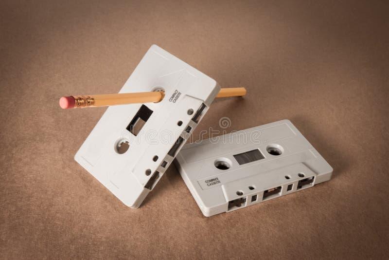 Cassetes de banda magnética com o lápis para a rebobinação no fundo do papel marrom Estilo do vintage imagens de stock