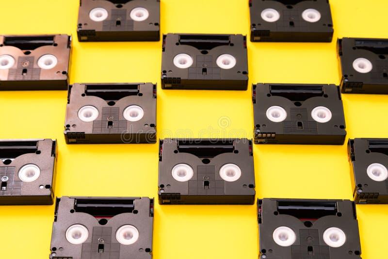 Cassetes de banda magnética do vintage mini DV usadas filmando para trás em um dia Teste padrão feito de video tapes plásticos no imagem de stock