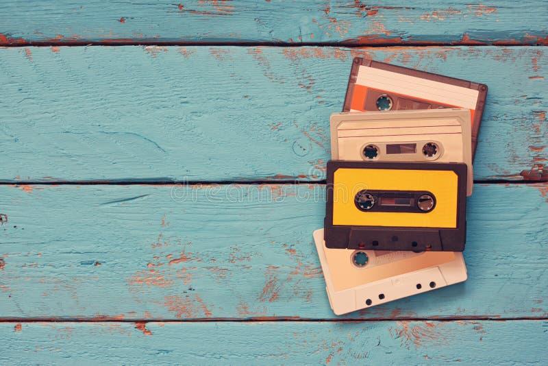Cassetes de banda magnética sobre a tabela de madeira textured azul Vista superior filtro retro imagem de stock