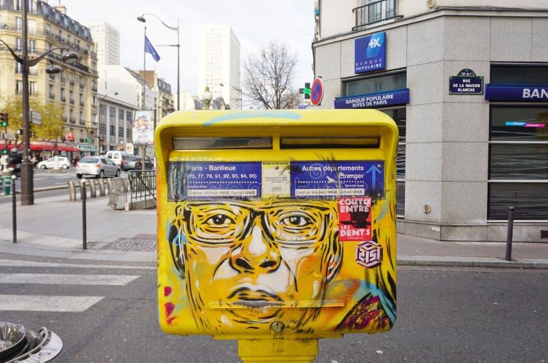 Cassetta delle lettere gialla dipinta coperta di arte della via dal muralista francese C215 dei graffiti a Parigi immagine stock