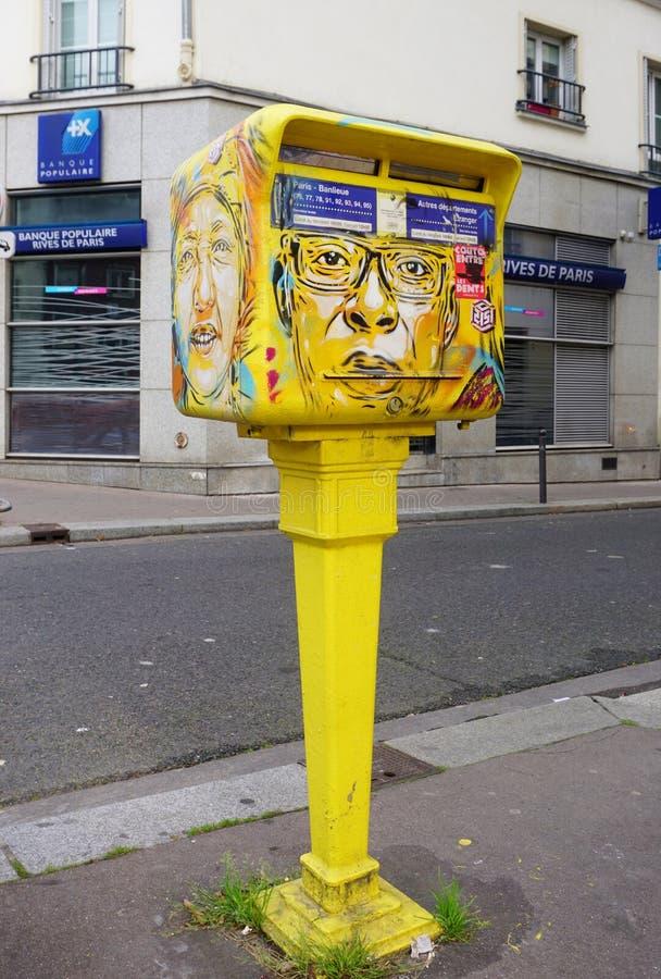 Cassetta delle lettere gialla dipinta coperta di arte della via dal muralista francese C215 dei graffiti a Parigi immagine stock libera da diritti