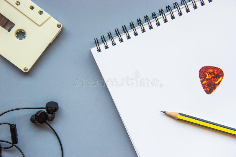 Cassette, écouteurs, crayon, sélection de guitare et carnet vide photo libre de droits