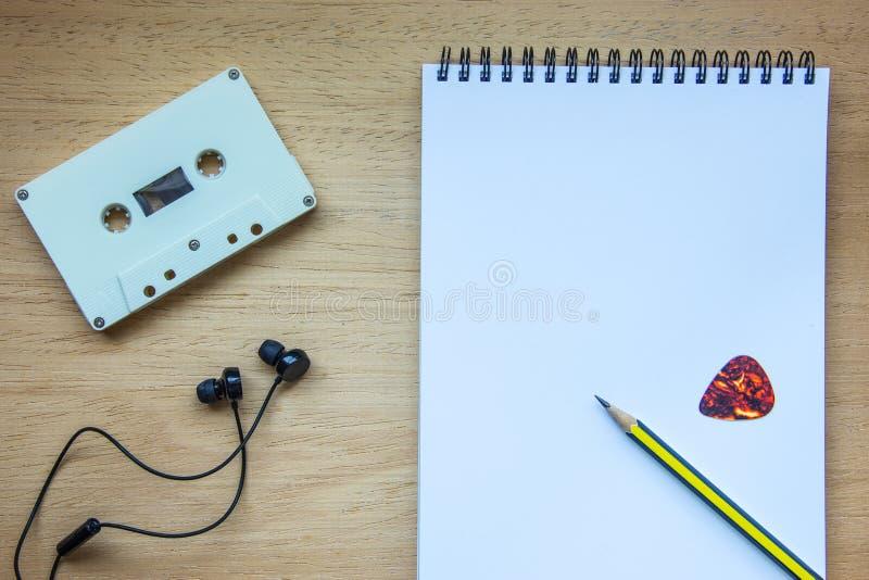 Cassette, écouteurs et carnet vide sur le bois pour le compositeur photos libres de droits