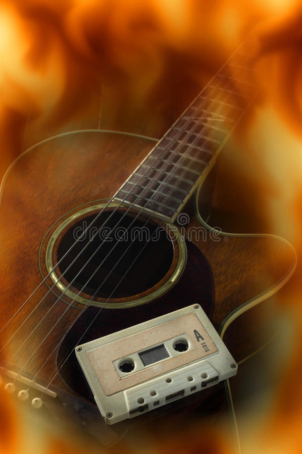 Cassette on acoustic guitar,fire flame screen. Cassette tape on acoustic guitar,fire flame screen royalty free stock image