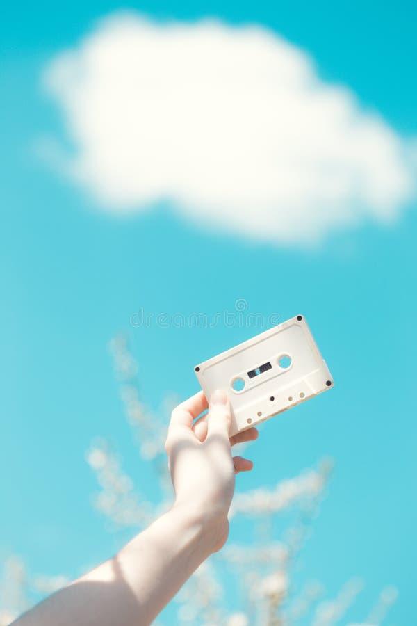 Cassette dans les mains de la fille contre le ciel bleu photo stock