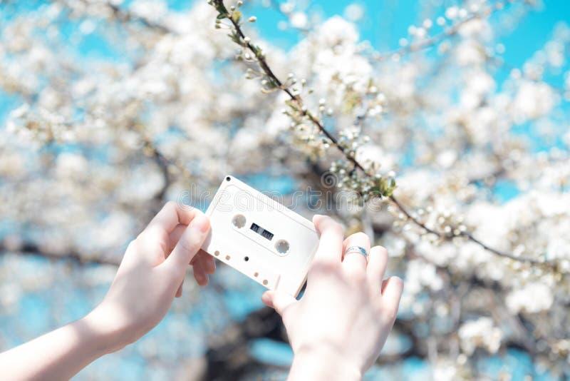 Cassette dans les mains de la fille contre le ciel bleu photos libres de droits