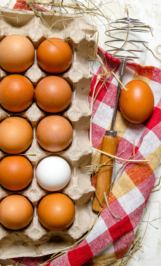 The cassette with eggs, hay and whisk on the fabric. stock photos