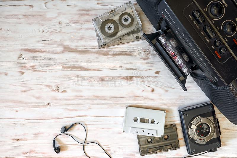 Cassette player, cassette recorder and audio tape on a wooden ba. Ckground stock photos