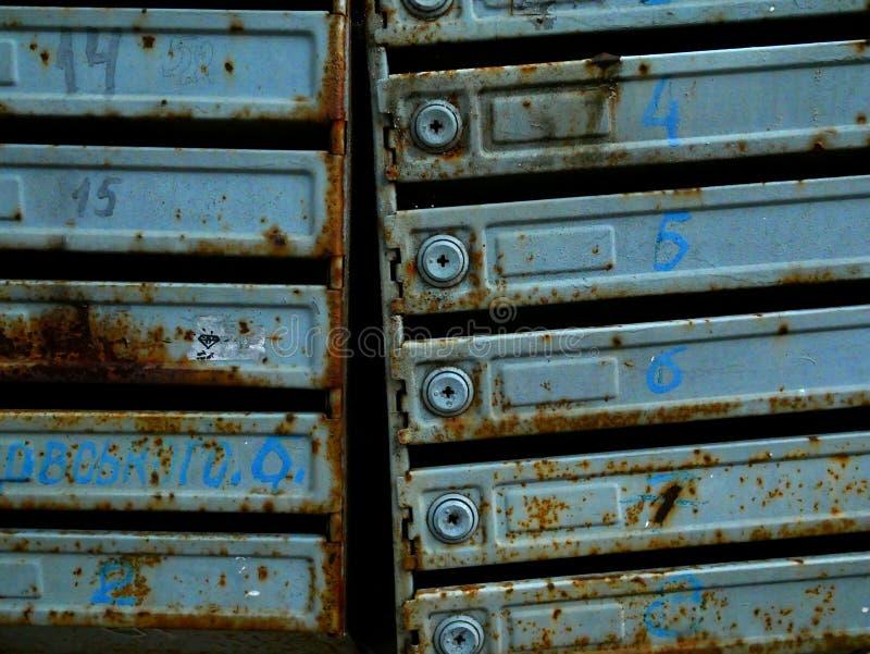 Cassette postali antiche in un palazzo di appartamenti ruggine e trama fotografia stock