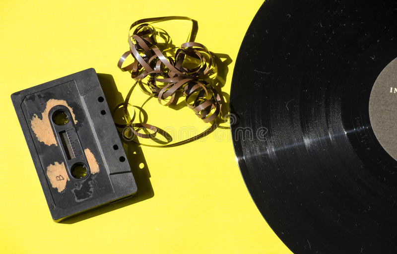 Cassette and vinyl record on a colored background yellow royalty free stock photos