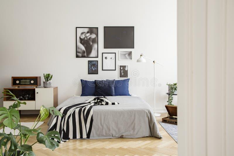 Cassettone di legno bianco accanto al letto con i cuscini blu scuro, il piumino grigio e la coperta in bianco e nero barrata in c fotografie stock libere da diritti