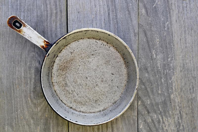 Cast iron antique frying pan on grey vintage rustic background stock photo