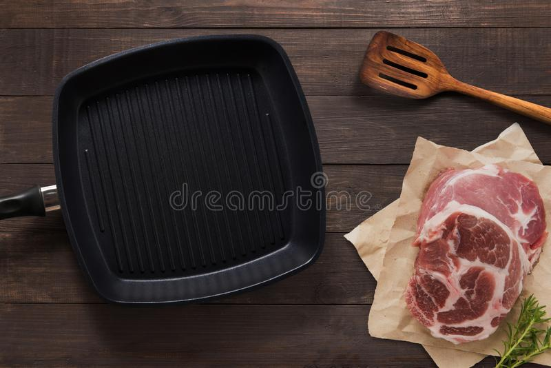 Cast iron griddle pan and beef steak wood on wooden background. Top view, Copy space. royalty free stock photo