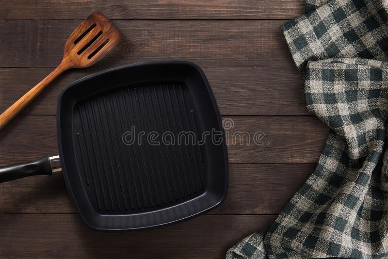 Cast iron griddle pan and turner wood on wooden background. Top view, Copy space. stock photo