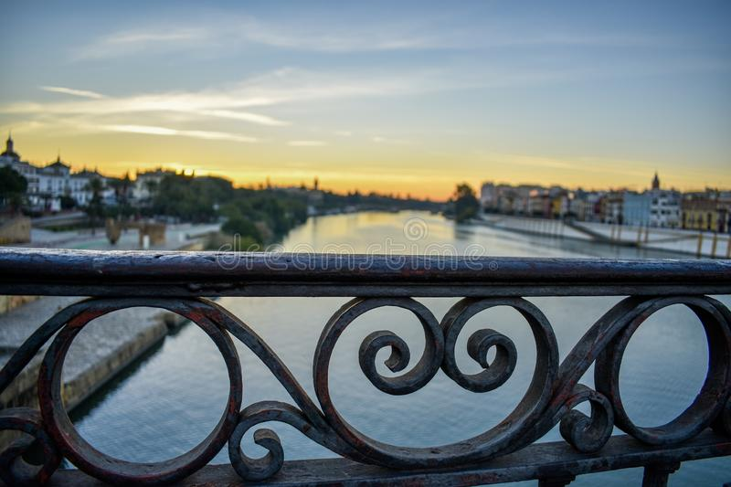 A cast iron handrail of a bridge at sunrise in Seville, Spain. The cast iron curls of a bridge handrail cuts across the still water of the Guadalquivir river in royalty free stock photography