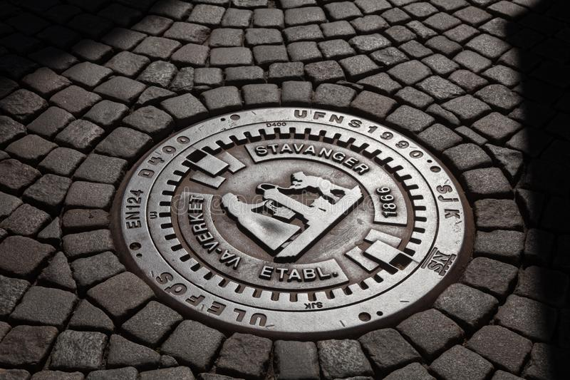Manhole cover on cobblestone street in Stavanger Rogaland Norway Scandinavia. Cast iron manhole cover on a cobblestone street in a city of Stavanger, Rogaland stock image