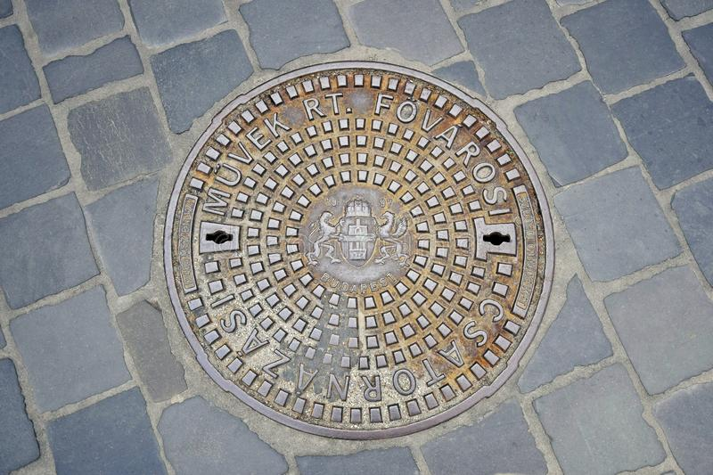 Cast iron ornamented manhole cover in Budapest, Hungary. Closeup of duct  manhole cover with Budapest Coat of Arms at the Old Town royalty free stock image